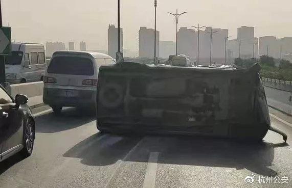 杭州早高峰一面包车高架上爆胎侧翻 几十名车主合力抬车