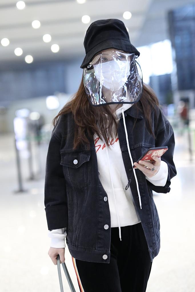 张萌戴黑色渔夫帽现身机场 猫咪手机壳暴露少女心