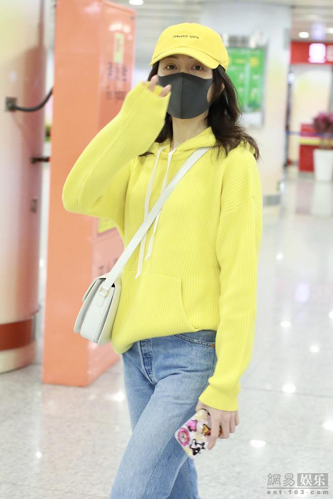 王鸥穿黄色卫衣现身机场 回眸甜笑挥手比V