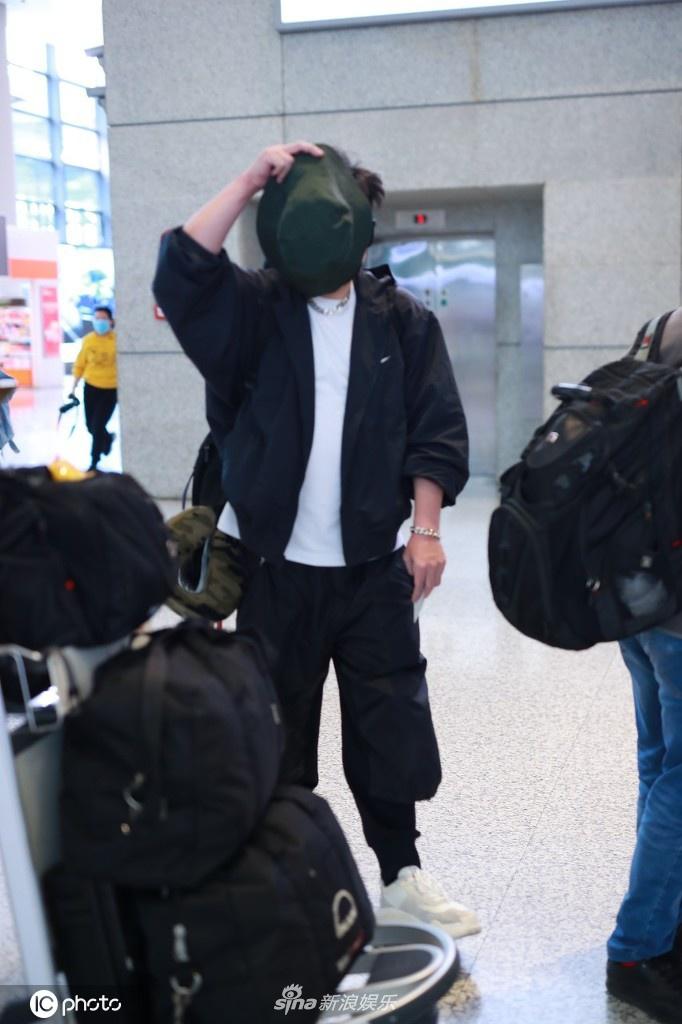 钱枫穿一身黑衣现身机场 高举帽子遮脸防止被拍