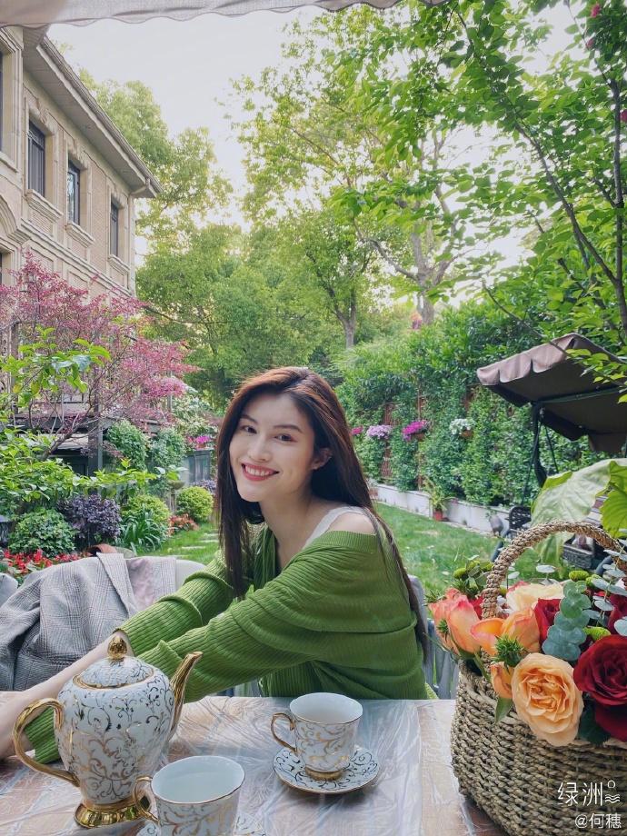 何穗分享春日穿搭 着绿色开衫置身花园清新悠闲