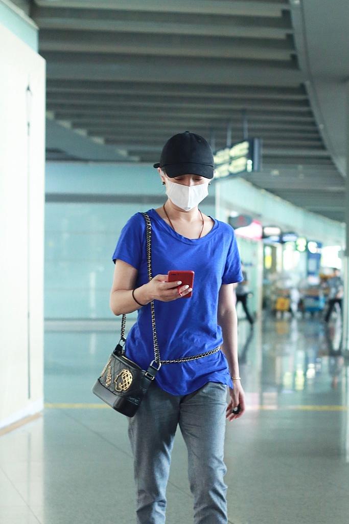 周迅穿蓝紫色T恤 巧背挎包展时尚态度
