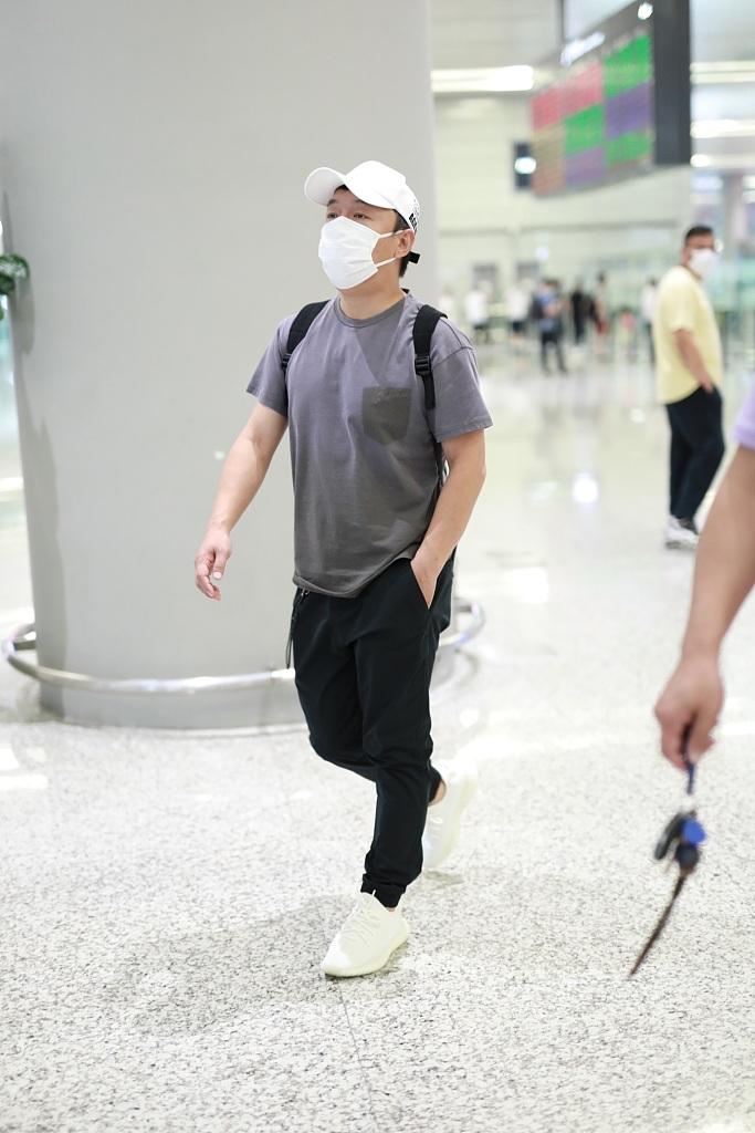 黄渤灰色T恤配白色鸭舌帽 装扮低调单手插兜赶路