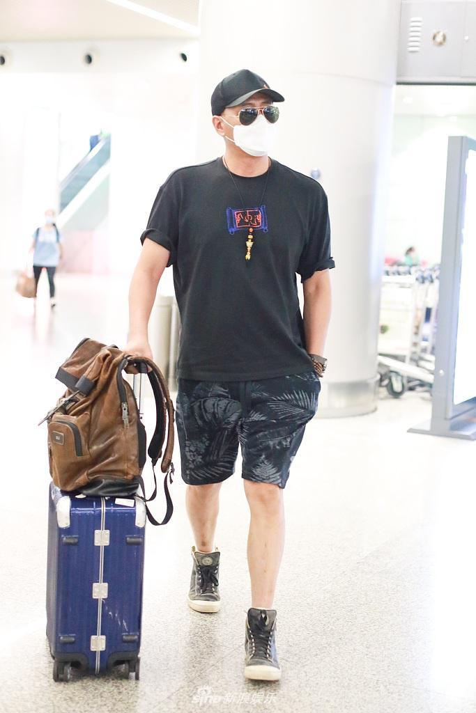 胡军穿黑装架黑超变身潮大叔 插兜走机场潇洒帅气