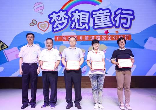 中国道路交通安全协会秘书长王京(左一)给讲师授牌