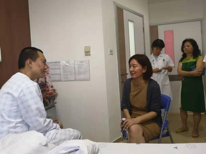 卢新宁看望《环球时报》记者付国豪。(图片来源:中央政府驻港联络办)