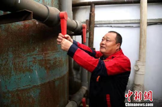 供热工人打开锅炉注水阀门,为锅炉补水。 冯宏伟 摄
