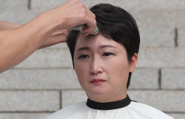 10日,韩国女议员李彦周当众剃光头,流下泪水(韩联社)