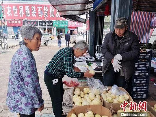 7月23日(大暑)一早,漠河当地商贩穿羽绒服卖菜。 姜辉 摄