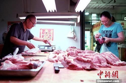 资料图:市民正在购买猪肉。中新社记者 张远 摄