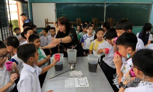清熱涼茶以蜜糖或黃糖調味,學生們喝得津津有味。(馬來西亞《星洲日報》/李祝福 攝)