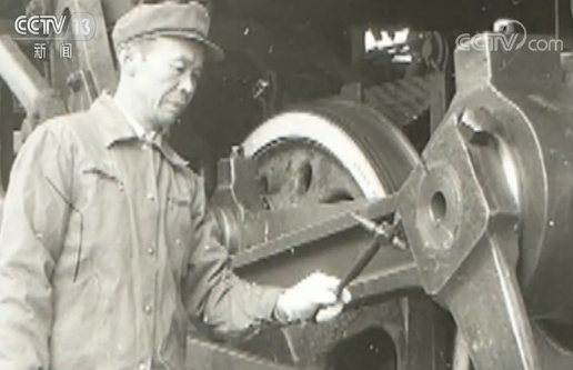 上世纪70年代,江西省南昌市向塘机务段司机长使用点检锤检查火车头轮对部件;
