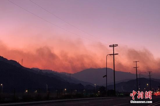 资料图:洛杉矶市遭遇山火,山头腾起滚滚浓烟。中新社记者 张朔 摄