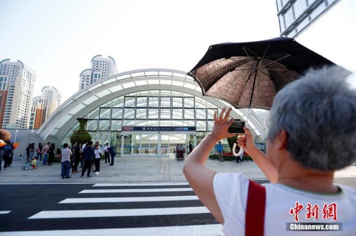 旅客在草桥站外拍照。中新社记者 富田 摄