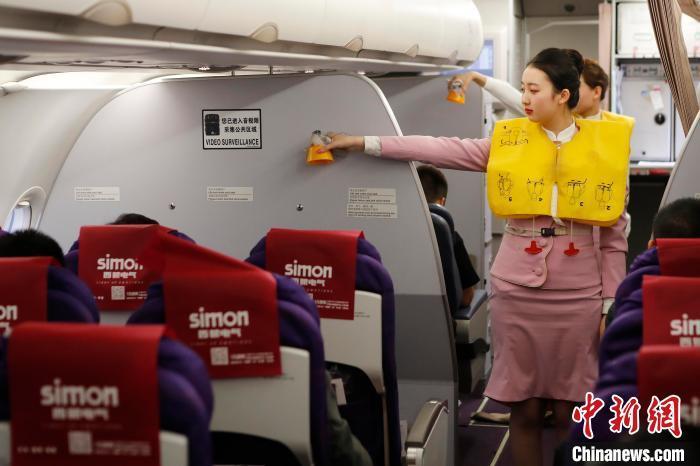 王姝樱在客舱里做着安全演示。 殷立勤 摄