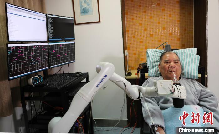 """图为高位截瘫患者张先生用""""意念""""喝可乐 浙大供图 摄"""