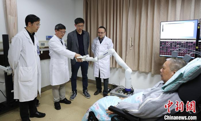 """图为高位截瘫患者张先生用""""意念""""和研究团队握手 浙大供图 摄"""